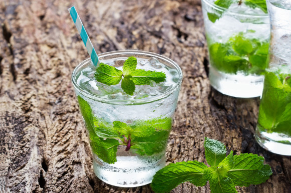 glass of cold water with fresh mint leaves and ice cubes on wooden background